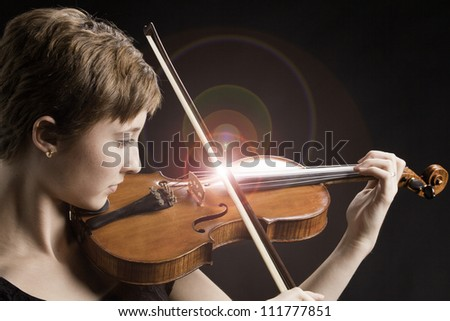Intense teenage female girl with red brown hair isolated playing violin with on a black background.