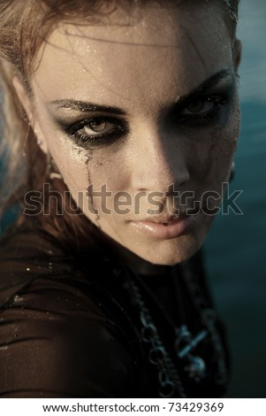 Intensive makeup girl spreads her tears and water. She is upset and thoughtful, does not know what to do and looks at you.
