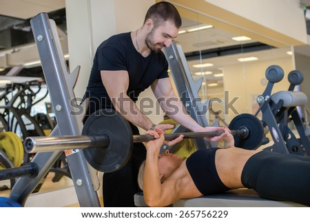 Intensive training together. Couple of young and beautiful people is having workout in a gym. Perfect shape. Sportsmen. Hard workout in a gym