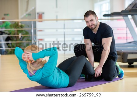 Intensive training together. Couple of young and beautiful people is having workout in a gym. Both are having abdominals training. Perfect shape. Sportsmen. Good workout in a gym - stock photo
