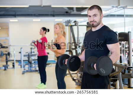 Intensive training together. Portrait of young and handsome strong athlete man in a gym. Two athlete girls are training on the background. Perfect shape and proper training.