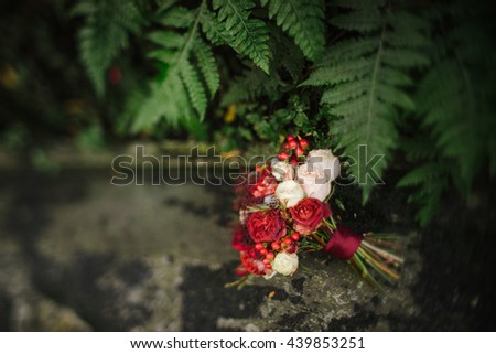 Intentionally blurred image of a bouquet of red and white flowers and berries on the floor of vintage greenhouse. Tilt-shift lens used, soft selective focus. - stock photo