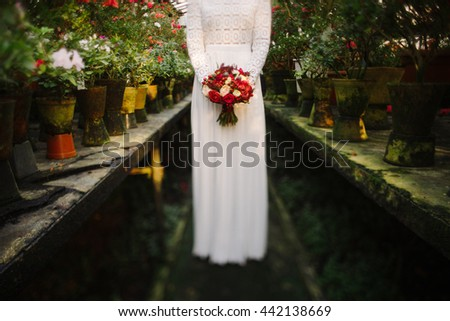 Intentionally blurred image of a bride in white simple dress hold a bouquet of red flowers in her hands. Tilt-shift lens used, soft selective focus. - stock photo