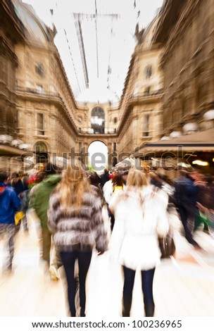Intentionally motion blurred creative image of people walking in Galleria Vittorio Emanuele II in Milan, Italy. The gallery is one of the most famous landmarks in Milan and a famous shopping street. - stock photo