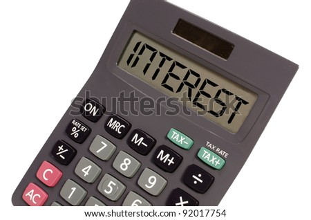 interest written on display of an old calculator on white background in perspective - stock photo