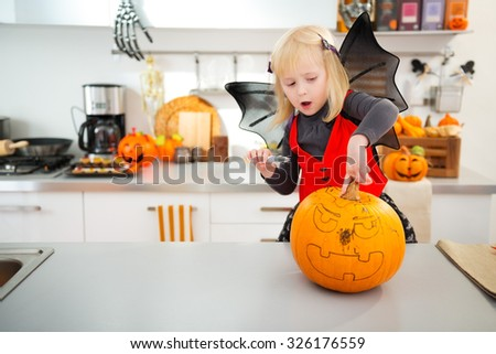 Interested blond girl in bat costume using stencils to carve big orange pumpkin Jack-O-Lantern on Halloween party in decorated kitchen. Traditional autumn holiday - stock photo