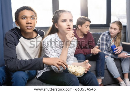 Interested teenagers sitting on sofa and eating popcorn from bowl indoors