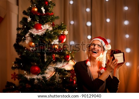 Interested woman near Christmas tree shaking present box trying to guess what's inside - stock photo