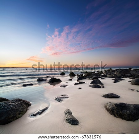 interesting beach at twilight with rocks in foreground - stock photo