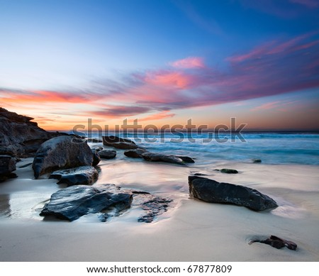 interesting beach with rocks in foreground and red clouds on sky - stock photo