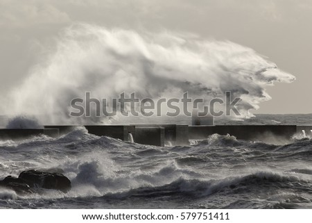 Interesting big stormy sea wave splash and spray. Douro river mouth north new pier, Porto, Portugal, in January.