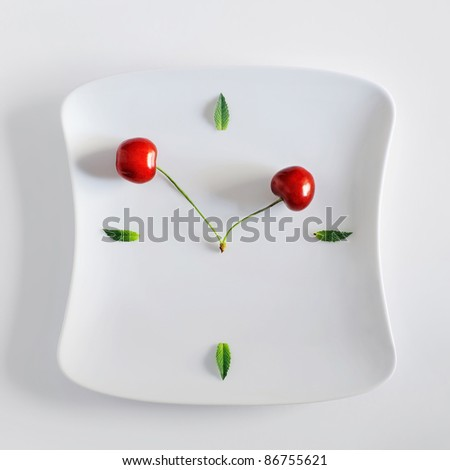 interesting clock dial made of a plate, green leaves and clock hands made of cherries - stock photo