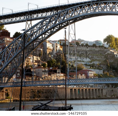 Interesting composition with the D. Luis bridge and the masts of the rabelo boats seeing in the background a traditional neighborhood of Porto at dawn - stock photo