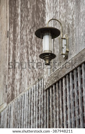 Interesting historical lantern on the wooden wall