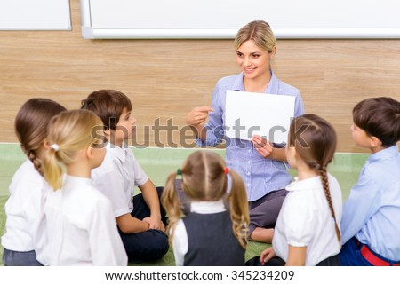 Interesting lesson. Young female teacher successfully communicating with her pupils by discussing a picture. - stock photo