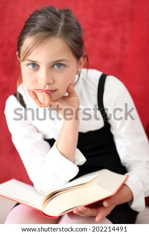 Interesting reading - girl reading a book .Child reading a book .Joyful girl reading a book sitting on the orange chair  - stock photo