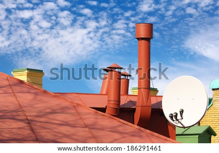 Interesting roof detail: pipes and a satellite dish - stock photo