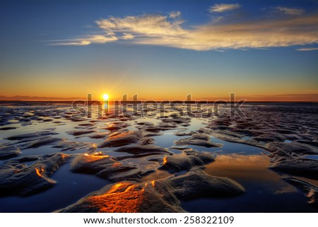 Interesting sandy formations at a beach at sunset - stock photo