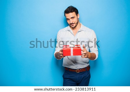 interesting sexy man with a red christmas gift on blue background - stock photo