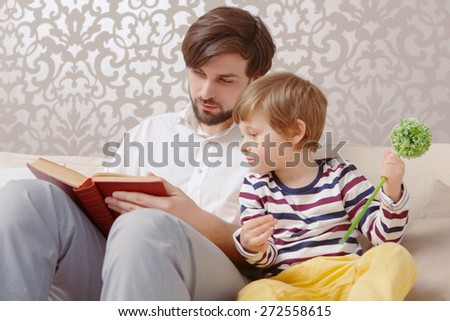 Interesting story. Portrait of a young man reading a book with his small son holding a toy