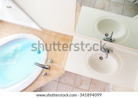 Interior architecture of full bathtub and acrylic sink with faucets - stock photo