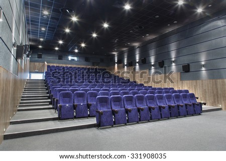 Interior cinema hall with plenty of seating and a projector.