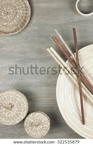 Interior decor: natural wooden dish with sticks and baskets on gray shabby wood background. Top view point. - stock photo
