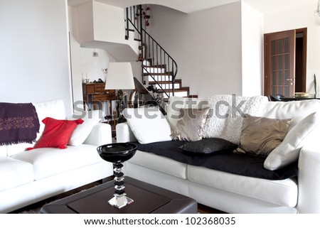 Interior decoration of a modern loft, white sofa and stairs