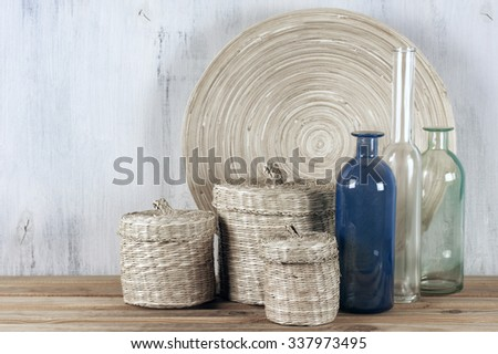 Interior decorations: wooden dish, baskets and glass bottles on rustic wooden background. - stock photo