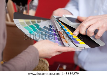 Interior decorator in a meeting with a client discussing various paint colors from a colorful set of swatches he is holding in his hand - stock photo