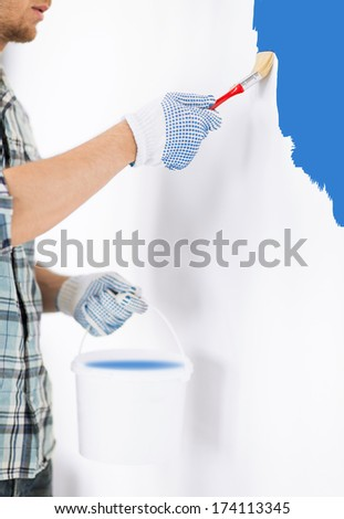 interior design and home renovation concept - man hands with paintbrush and paint pot painting wall - stock photo