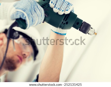 interior design and home renovation concept - man in helmet with electric drill making hole in wall - stock photo