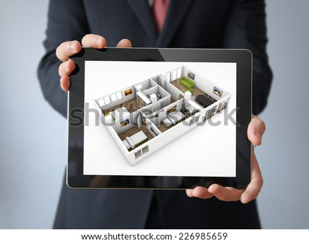 interior design concept: businessman with a tablet with interior design app on the screen - stock photo
