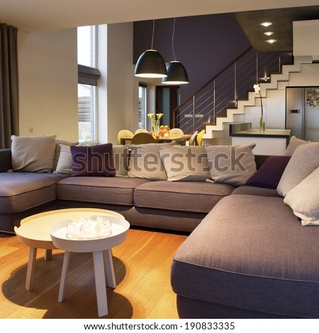 Interior design - cozy living room at foreground and kitchen with dinning table at background  - stock photo