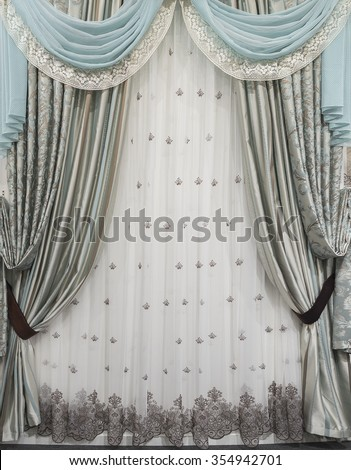 Interior design in a classic and luxurious style. Combined curtains, tulle and pelmet on the window. - stock photo