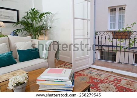 Interior design lifestyle of a home living room with white sofa and cushions, interior view. House indoors with carpets and open french doors balcony. Tranquil and aspirational lifestyle home space. - stock photo