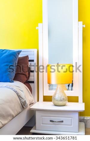 Interior Design: Modern Bedroom, White Wooden bedside table and reading lamp./ Interior Design: Modern Bedroom, Bedside cabinet. - stock photo