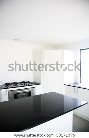 Interior design of a kitchen with black benchtop and white cupboards. - stock photo