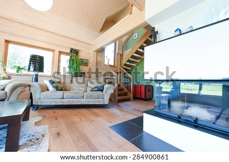 Interior design of a light and comfortable living room in a modern wooden log house. - stock photo