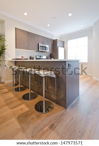 Interior design of a luxury modern kitchen with some sits at the counter. Vertical. - stock photo