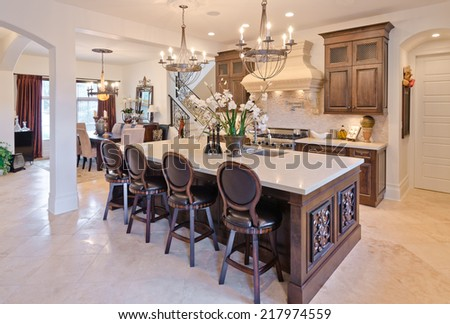 Interior design of a luxury modern kitchen with the counter and some chairs.