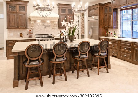 Interior design of a luxury stylish modern kitchen with the counter and some chairs  behind. - stock photo