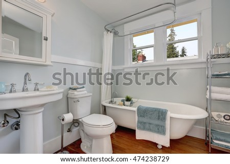 Interior design of craftsman bathroom with a pedestal sink, a freestanding tub, a toilet, white tile, pastel blue walls and hardwood floors. Northwest, USA