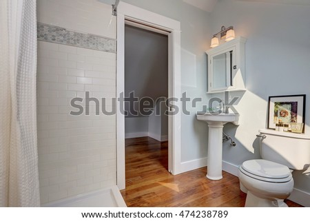 Interior design of craftsman bathroom with a pedestal sink, a toilet, white tile, pastel blue walls and hardwood floors. Northwest, USA