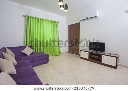 Interior design of luxury apartment living room area with TV and cabinet - stock photo