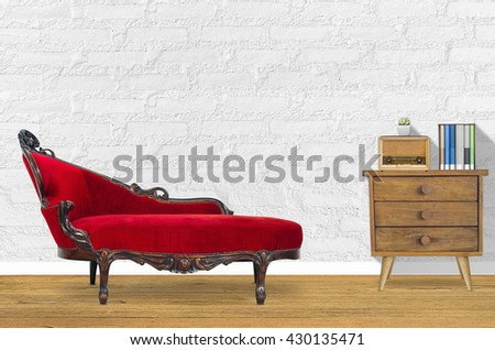 Interior design with red chair in fornt of white wall with plant, books, old Radio on old wooden dresser.