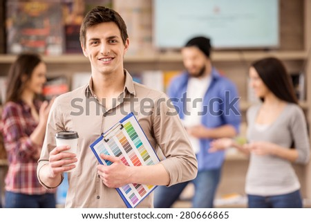 Interior designer dressed casual looking at camera and smiling. Coffee break at office. - stock photo