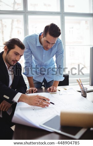 Interior designer explaining blueprint to male coworker in office - stock photo