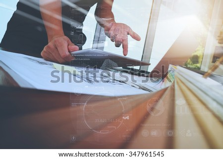 Interior designer hand working with new modern computer laptop and pro digital tablet with sample material board and digital design diagram layer on wooden desk as concept - stock photo