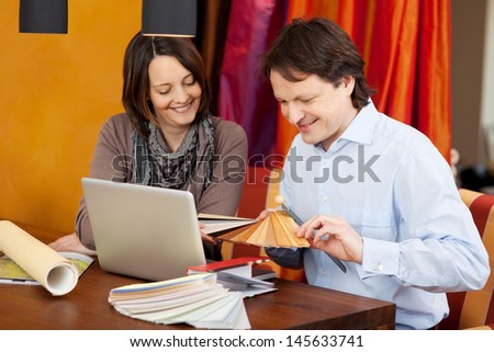 Interior designer in a client meeting sitting at a desk with an attractive woman showing her various samples - stock photo